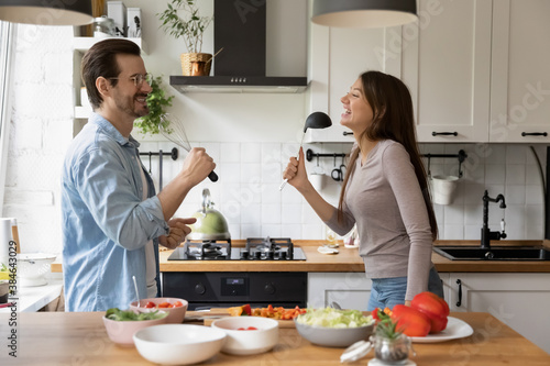 Obraz na plátně Side view emotional young handsome man having fun with pretty wife, singing songs using utensils as microphones in modern kitchen, playful family couple enjoying free weekend leisure time together