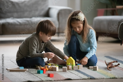 Cute little preschooler boy and girl children sit on warm floor in living room play with building blocks together. Small kids siblings have fun engaged in funny game or activity with bricks at home.