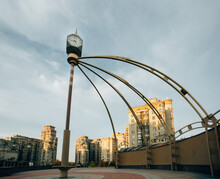 Old Street Clock In The Middle Of A Moscow Housing Estate With Cloudy Skies And Multi-storey Apartment Buildings In The Background. It Is A Wide Angle Shot From Low-ground Level.