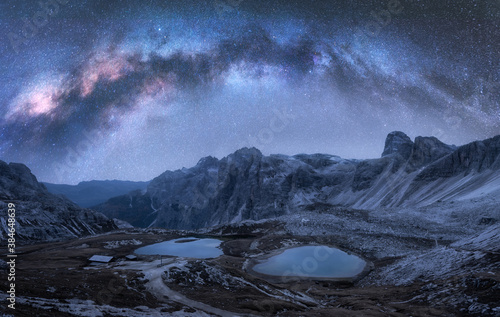 Milky Way arch over mountains at night in summer. Landscape with alpine mountains, lake, purple sky with arched milky way and stars, reflection in water, high rocks. Dolomites, Italy. Space and galaxy