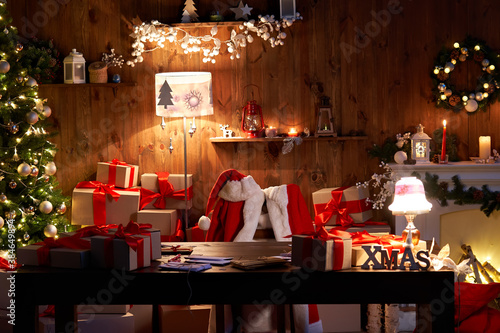 Fotomural Santa Claus costume and hat hanging on chair at table with Merry Christmas decor gifts presents on holiday eve in cozy Santa home workshop interior late in night with light on xmas tree and fireplace