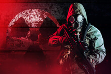 Photo Of A Post Apocalyptic Stalker Soldier In Gas Mask And Hood Jacket Holding Rifle And Standing On Dark Rusty Metal Wall With Radiation Sign And Red Glowing Light.