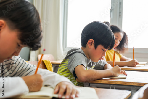Fotografie, Obraz Asian school children sitting at desk in school writing in note book with pencil, studying, education, learning