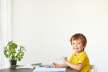 4 Years Old Child Cute Boy Draws At The Table And Looks At The Camera On A White Background
