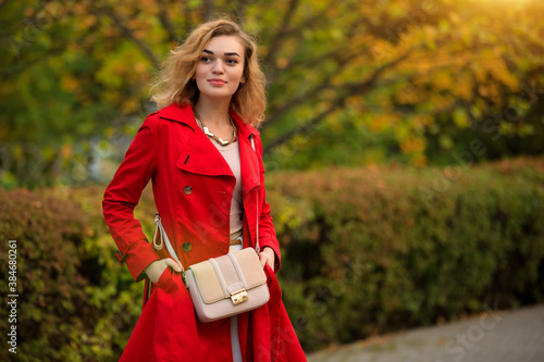 Fototapeta Portrait of woman in red coat at autumn alley