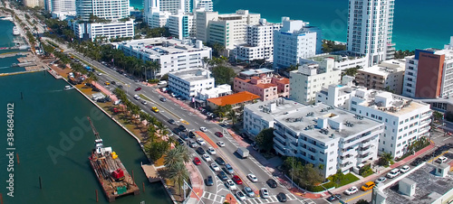 Obraz Miami Beach aerial view, Florida from drone viewpoint. Indian Creek and city skyline on a wonderful sunny day, slow motion. - fototapety do salonu