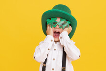 Smiling Little Child Boy In Green Leprechaun Hat On Yellow Background. St. Patrick Day Celebration. Funny Face