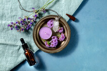 Aromatherapy Banner Design With Copy Space. Incense Cone, Essential Oil, Scented Candle, Perfume Vial, Vervain And Lavender, Shot From The Top With A Place For Text On A Blue Background