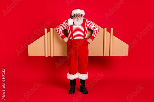 Full length body size view of his he handsome strict bearded Santa father wearing jet air wings celebrate eve noel newyear isolated bright vivid shine vibrant red color background - 384712824