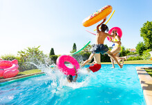 Group Of Happy Teenage Kids With Inflatable Toys Jump And Splash Into Water Pool Jumping Together View From Side