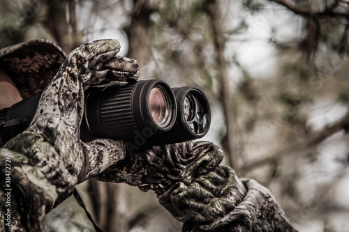 hunter in a camouflage suit looks through binoculars on the hunt, close-up, soft Fototapeta