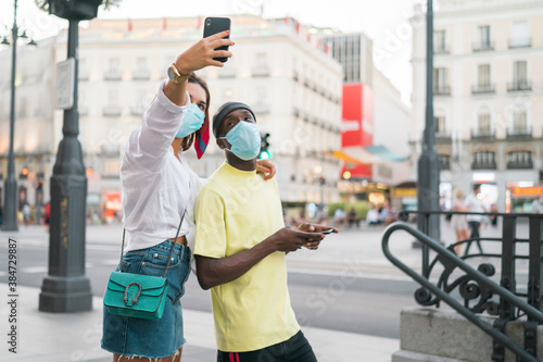 Photo Caucasian woman making a self portrait with an african man against city wearing