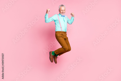 Full length body size side profile photo of smiling elder man jumping high wearing retro clothes isolated on pink color background - 384733027