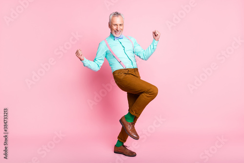 Full length body size side profile photo of happy old man smiling gesturing like winner isolated on pink color background