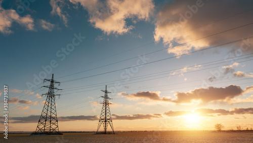 Fototapeta Power lines during a beautiful winter sunset.