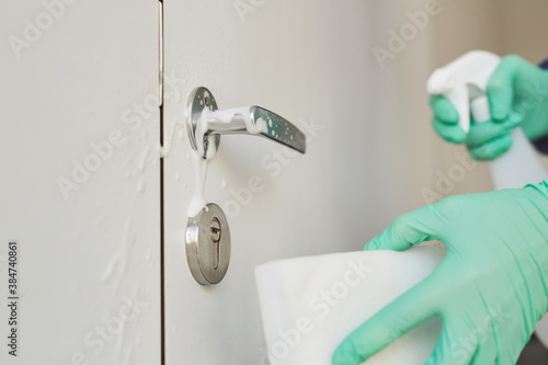 Close up of unrecognizable sanitation worker wearing gloves cleaning door handle Canvas