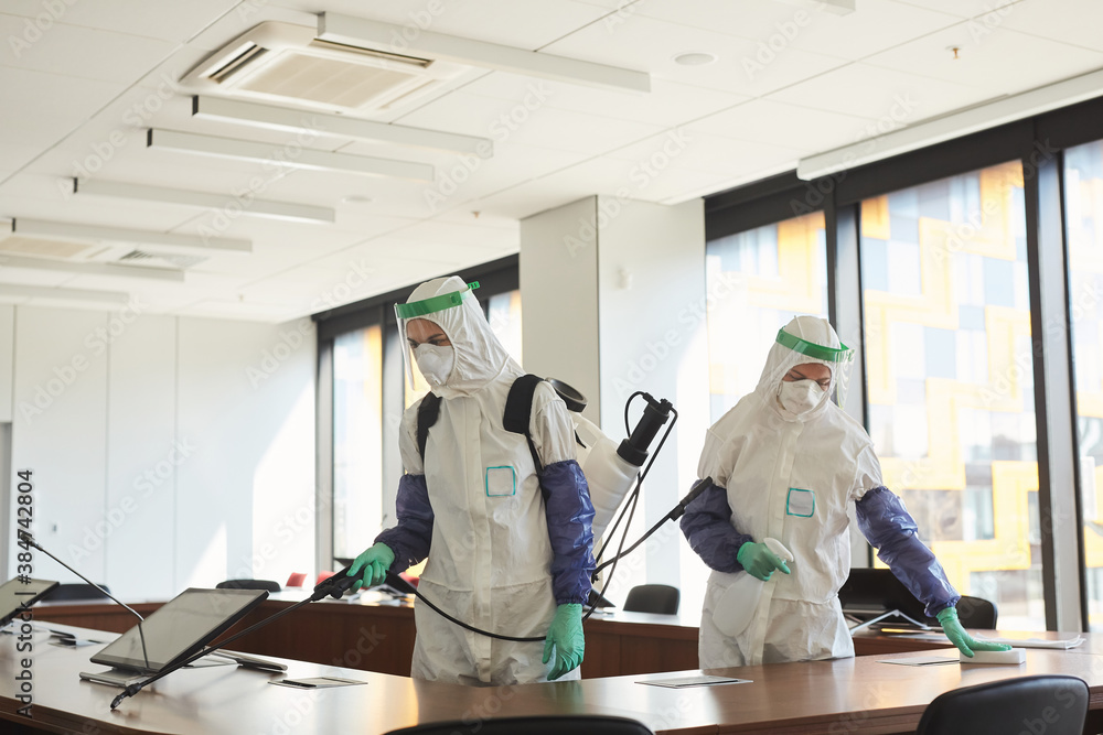 Fototapeta Wide angle portrait of two sanitation workers wearing hazmat suits cleaning and disinfecting conference room in office, copy space