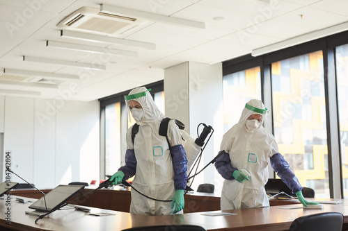 Fotografija Wide angle portrait of two sanitation workers wearing hazmat suits cleaning and