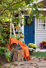 Cozy Autumn Patio With Chair, Plaid, Plants, Wooden Lantern, Potted Chrysanthemums. Halloween. Decorations In Backyard For Relax In Autumn Garden. Stylish Fall Decor On Front Porch Home. Thanksgiving