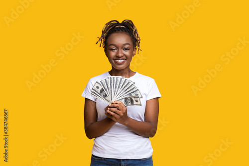 Happy black woman holding money on yellow background