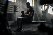 Serious Sportsman Sit On Bench And Lift Dumbbells .