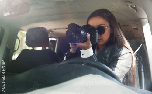 Private detective with camera spying from car Fotobehang