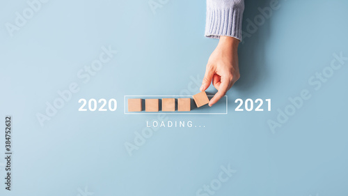 Obraz na plátne Loading new year 2020 to 2021 with hand putting wood cube in progress bar