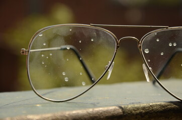 Water droplets on Eye glasses, green blurred background.