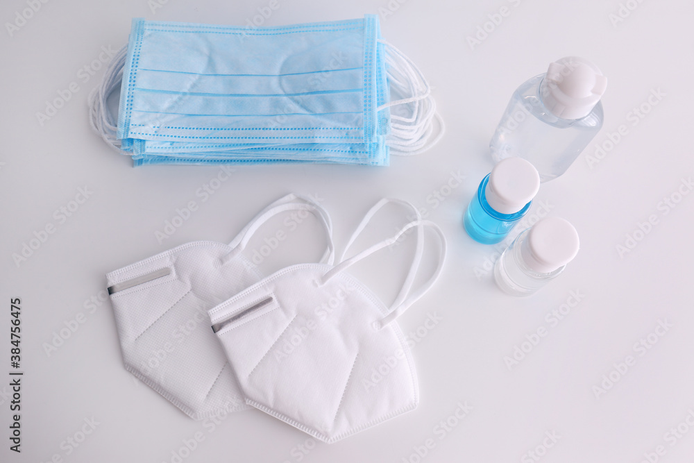 Fototapeta Hand sanitizers and respiratory masks on white background, flat lay. Protective essentials during COVID-19 pandemic