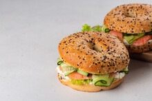 Bagel With Smoked Salmon, Cream Cheese, Salad And Cucumber. Light Pink Background. Copy Space.