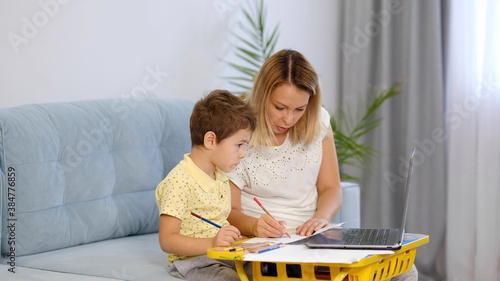 Photo young mother or nanny helps a little boy complete an assignment in an online school