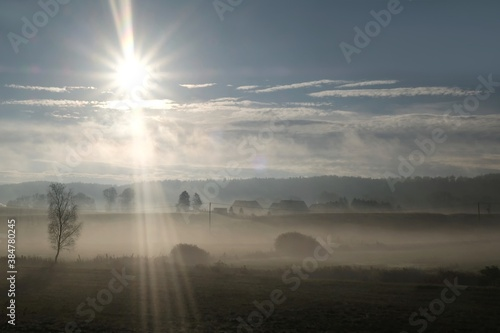 Cuadros en Lienzo Beautiful autumn moody landscape - fields and houses of village shrouded in mist in the morning