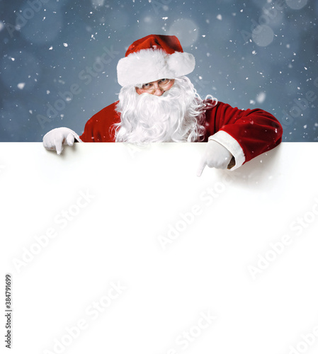 Happy Santa Claus pointing in blank white advertisement banner with copy space