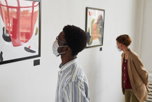 Portrait Of Two Young People Looking At Paintings While Wearing Masks At Modern Art Gallery Exhibition, Copy Space