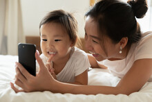Close Up Overjoyed Young Asian Mother And Adorable Little Daughter Using Smartphone Together, Lying On Cozy Bed, Looking At Screen, Taking Selfie, Watching Cartoons, Enjoying Leisure Time With Gadget