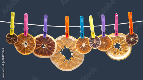 Fotografie, Obraz dried pieces of different citrus fruits hang on colored clothespins
