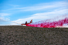 Emergency Response Airplane Drops Fire Retardant Over A Wildfire Going Behind A Desert Hill With Sagebrush