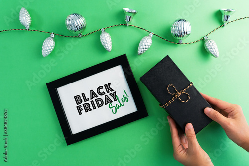 hand holding gift box with photo frame for Black Friday Sale con