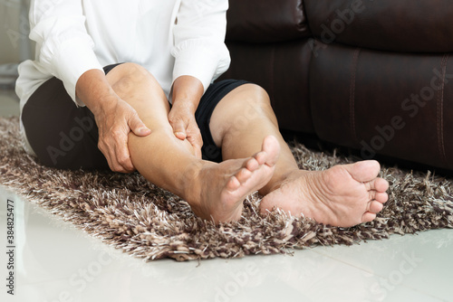 Photo leg cramp, senior woman suffering from leg cramp pain at home, h