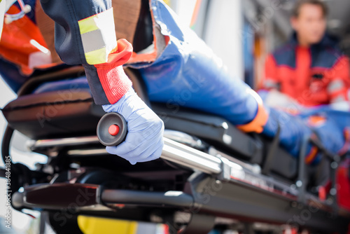 Obraz Selective focus of paramedic in latex glove holding stretcher with patient outdoors - fototapety do salonu