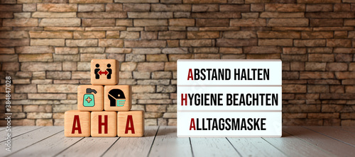Fototapeta German acronym AHA with a lightbox showing the three rules in a pandemic HOLD DI