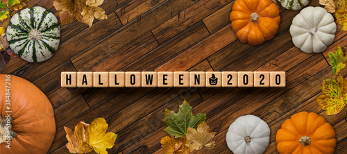 autumn decoration with pumpkins and colorful leaves and message HALLOWEEN 2020 on wooden background - 384847286