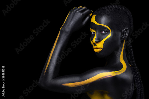 Obraz Face art. Woman with black and yellow body paint. Young african girl with colorful bodypaint. An amazing model with yellow makeup. Closeup face. - fototapety do salonu