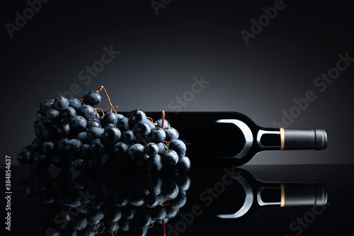Obraz Bottle of red wine and a bunch of grapes on a black reflective background. - fototapety do salonu