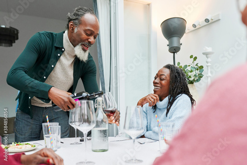 Smiling family having wine with dinner - 384856854