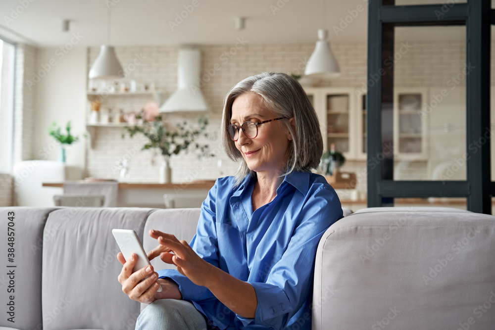 Fototapeta Relaxed mature old 60s woman, older middle aged female customer holding smartphone using mobile app, texting message, search ecommerce offers on cell phone technology device sitting on couch at home.