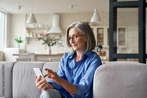 Relaxed mature old 60s woman, older middle aged female customer holding smartphone using mobile app, texting message, search ecommerce offers on cell phone technology device sitting on couch at home. - 384857043