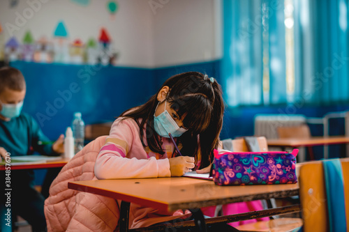 Elementary schoolchildren wearing a protective face masks  in the classroom Canvas Print
