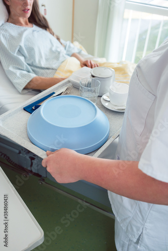 Obraz Nurse serving food in the hospital to a patient in bed - fototapety do salonu
