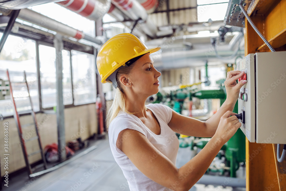 Fototapeta Experienced hardworking independent woman in working clothes with helmet on head standing next to dashboard and adjusting settings while standing in heating plant.